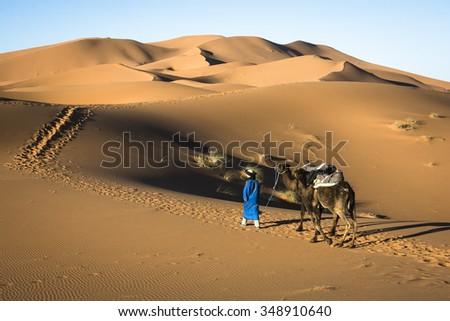 Sahara,Morocco-january 29 2015:A lonely camel men wearing traditional clothes crossing Sahara desert around the town named Merzouga in Erg Chebbi dunes,close to the Algeria border,Morocco. - stock photo