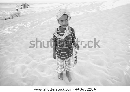 SAHARA, TUNISIA - SEPTEMBER 16, 2012 : Tunisian boy waiting for tourists so that he could sell souvenirs at a tourist stop in Ong Jemel, Tozeur, Tunisia. - stock photo