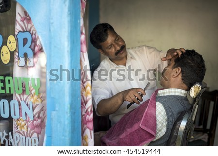 SAHARAN, INDIA - Jun 05, 2016: A barber shave the beard of a customer lying on antique barber chair inside hair saloon.