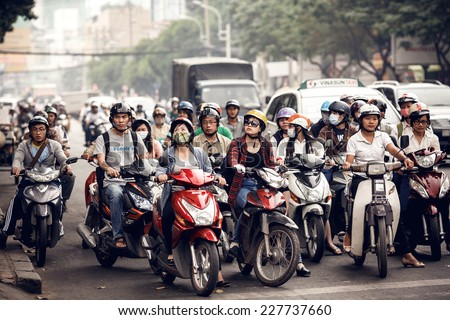 SAIGON - DECEMBER 28: Road traffic in Saigon, Vietnam on December 28,2013. In the biggest city in Southern Vietnam are more than 4 mil. motorbikes, the traffic is often congested. - stock photo
