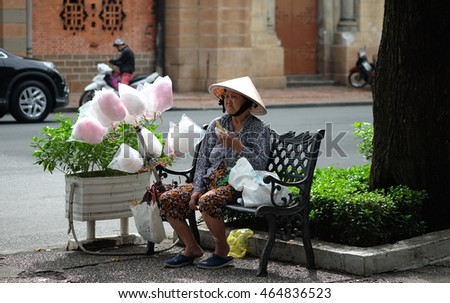 SAIGON, VIETNAM - 31 JUL, 2016: Unidentified old woman is sitting on the chair taking rest. She sells cotton candy as street vendor in Saigon city (Hochiminh city).