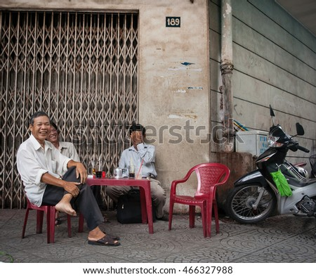 SAIGON, VIETNAM-OCTOBER 12;Three Vietnamese happy smiling men sit at plastic table and chairs with drinks and cigarette packets on street corner October 12, 2013  Saigon, Ho Chi Minh City Vietnam