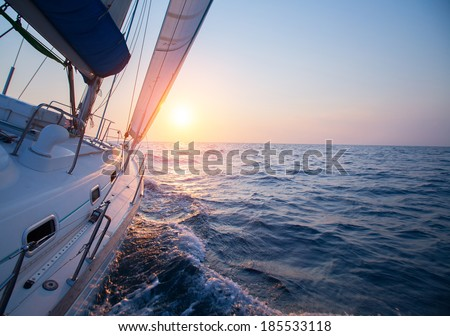 Sail boat in an open sea at sunset - stock photo
