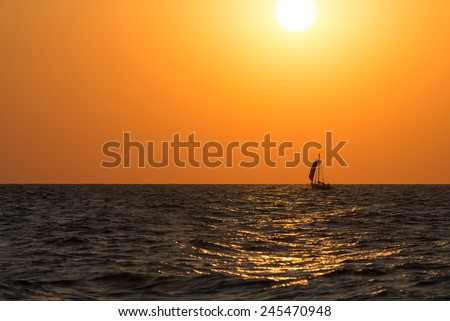 Sail boat is sea waves against bright sunset glow with golden sun way and large sun disc - stock photo