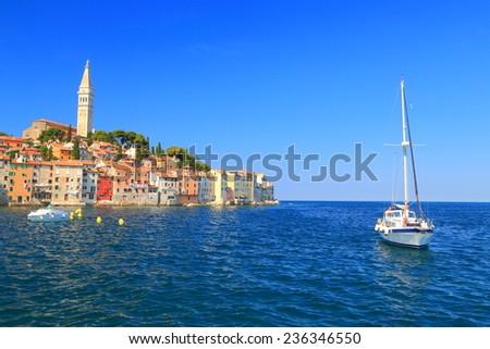 Sail boat navigates in the harbor of old Venetian town, Rovinj, Croatia - stock photo