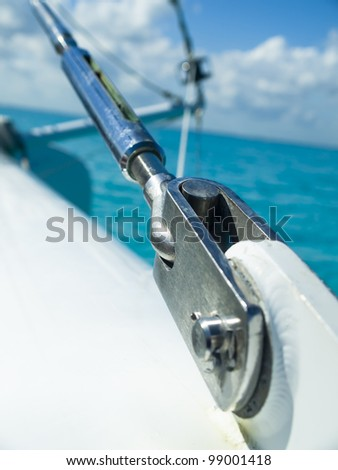 Sail boat stainless steal attachment cable over the ocean - stock photo