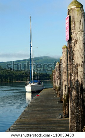 Sail boat tied to a weathered and worn wooden dock. - stock photo