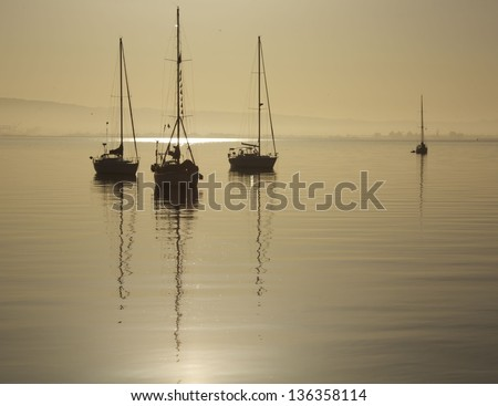 Sail boats setting on Calm water - stock photo