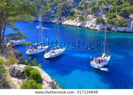 Sail boats surrounded by tall cliffs inside one of the calanques near Cassis, France - stock photo