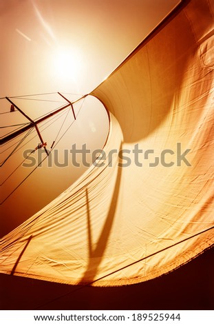 Sail fluttering in the wind on orange sky background, mild sunset light, sea cruise on luxury sailboat, summer vacation and holidays concept - stock photo