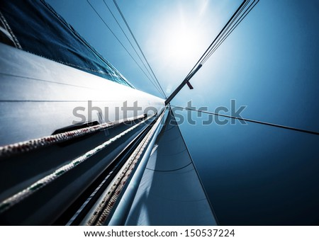 Sail over blue clear sky, abstract background, active lifestyle, detail of sailboat, luxury water transport, bright sun light, summer holidays concept - stock photo