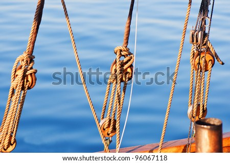 Sail yacht ropes and blocks on a water background - stock photo