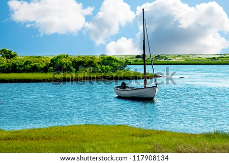 Sailboat anchored in a blue pond or lake, with green grass banks - stock photo