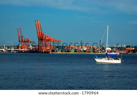 Sailboat & crane groups in Vancouver harbor. - stock photo
