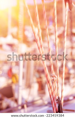Sailboat detail, ropes which holding sails in bright yellow sunset light, luxury and expensive water transport, travel and vacation concept - stock photo