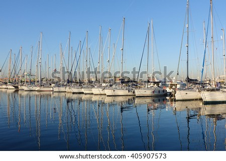 Sailboat harbor at sunset, many beautiful moored sail yachts in the sea port, modern water transport, summertime vacation, luxury lifestyle and wealth concept