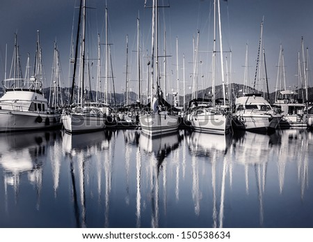Sailboat harbor in evening, many luxury moored sail yacht in the port, ship mast reflected in water, marina in European city, summer holidays  - stock photo