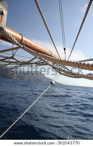 Sailboat in action, big white sail raised over blue clear sky - stock photo