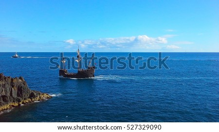 Sailboat in the ocean near the shore with breakwater. Atlantic Ocean, Madeira, Portugal