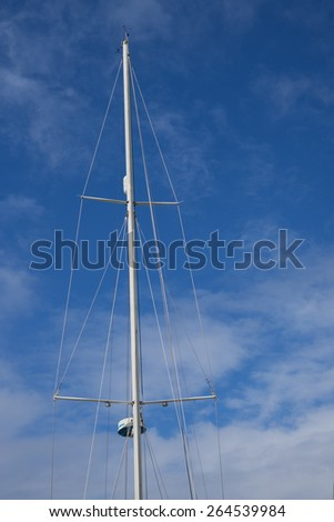 Sailboat mast and rigging against a blue sky with thin white clouds. - stock photo