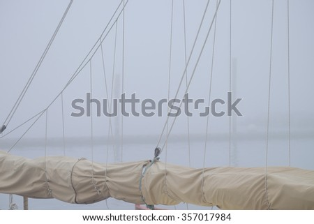 Sailboat masts and rolled up sails in heavy fog in a calm protected harbor   - stock photo