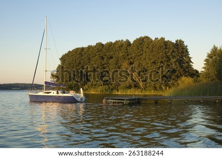 Sailboat moored by wooden jetty on a lakeshore at the break of dawn, Mazury, Poland - stock photo