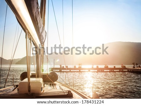 Sailboat on sunset, luxurious water transport, bright sun light on the sea, evening travel on sail yacht, summer vacation, yachting sport concept - stock photo