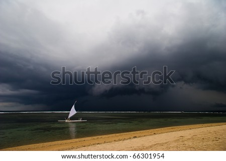 Sailboat on the horizon in bad weather - stock photo