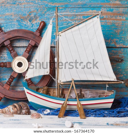 Sailboat or fishing boat made of wood as nautical decoration on wooden background - stock photo