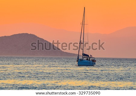 Sailboat Sailing on the beautiful Greek sea during the sunset - stock photo