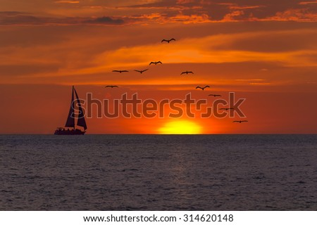 Sailboat sunset fantasy with a silhouetted boat sailing along its journey against a vivid colorful sunset with birds flying in formation against an orange and yellow color filled sky. - stock photo