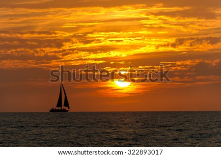 Sailboat sunset is a colorful vibrant orange and yellow cloudscape sunset.