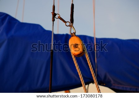 Sailboat tackle rope and pulley in front of blue wrapped sail on a two masted schooner - stock photo