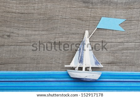 Sailboat with flag on wooden background - stock photo