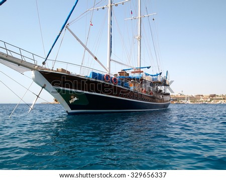 Sailboat with lowered sails against Egyptian shoe