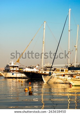 Sailboats anchored in harbor. Beautiful yachts are moored in the sea port. Private transport for luxury lifestyle on summertime and sea vacation. - stock photo