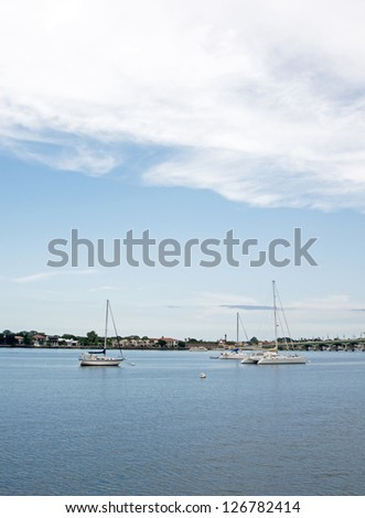 Sailboats cruising in the waters near a bridge in Saint Augustine, Florida. - stock photo