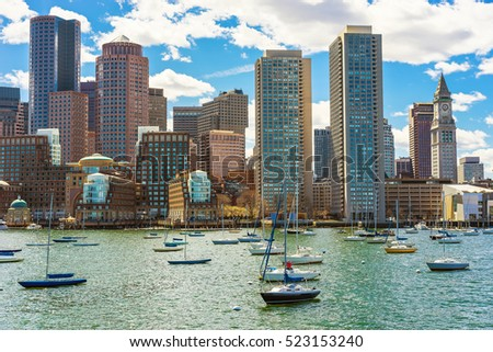 Sailboats floating in front of the skyline of the Financial District in Boston, USA. The city is located near many different water facilities. It is one of the oldest cities in the United States.