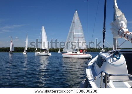 Sailboats floating on blue water of the lake.Russia. Competition sport of sailing.Yacht and beautiful seascape. Summer travel.