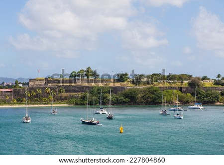Sailboats in bay off Martinique by old French Fort - stock photo