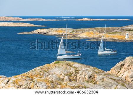 Sailboats sailing in rocky coast view - stock photo