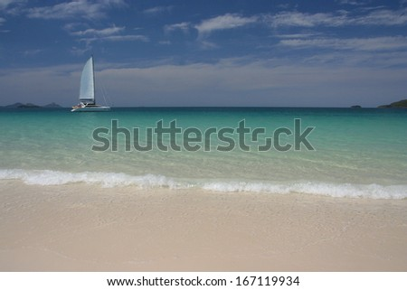Sailing along sandy beach - stock photo