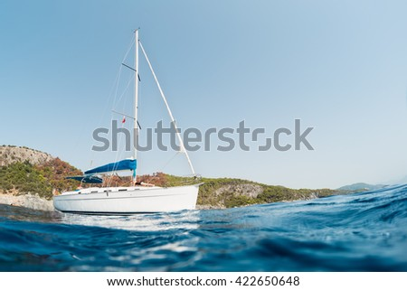 Sailing boat anchored in calm bay. - stock photo