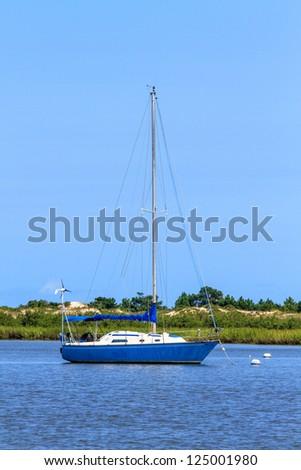 Sailing boat anchoring near beach coastline - stock photo