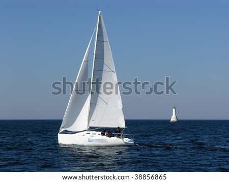 Sailing boat and lighthouse - stock photo
