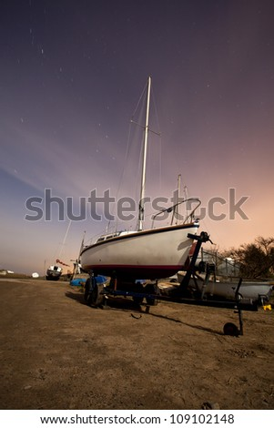 sailing boat at a boat yard on the wirral at night under the moon and stars