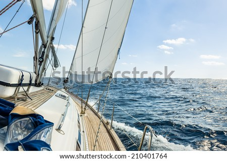 Sailing boat deck with hoisted sails and teak deck - stock photo