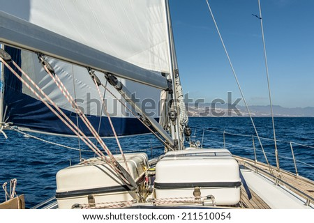 Sailing boat deck with sails up and liferafts