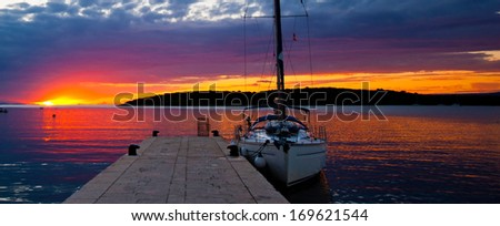 Sailing boat in marina at sunset - stock photo