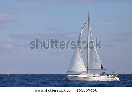 Sailing boat in open blue sea  - stock photo